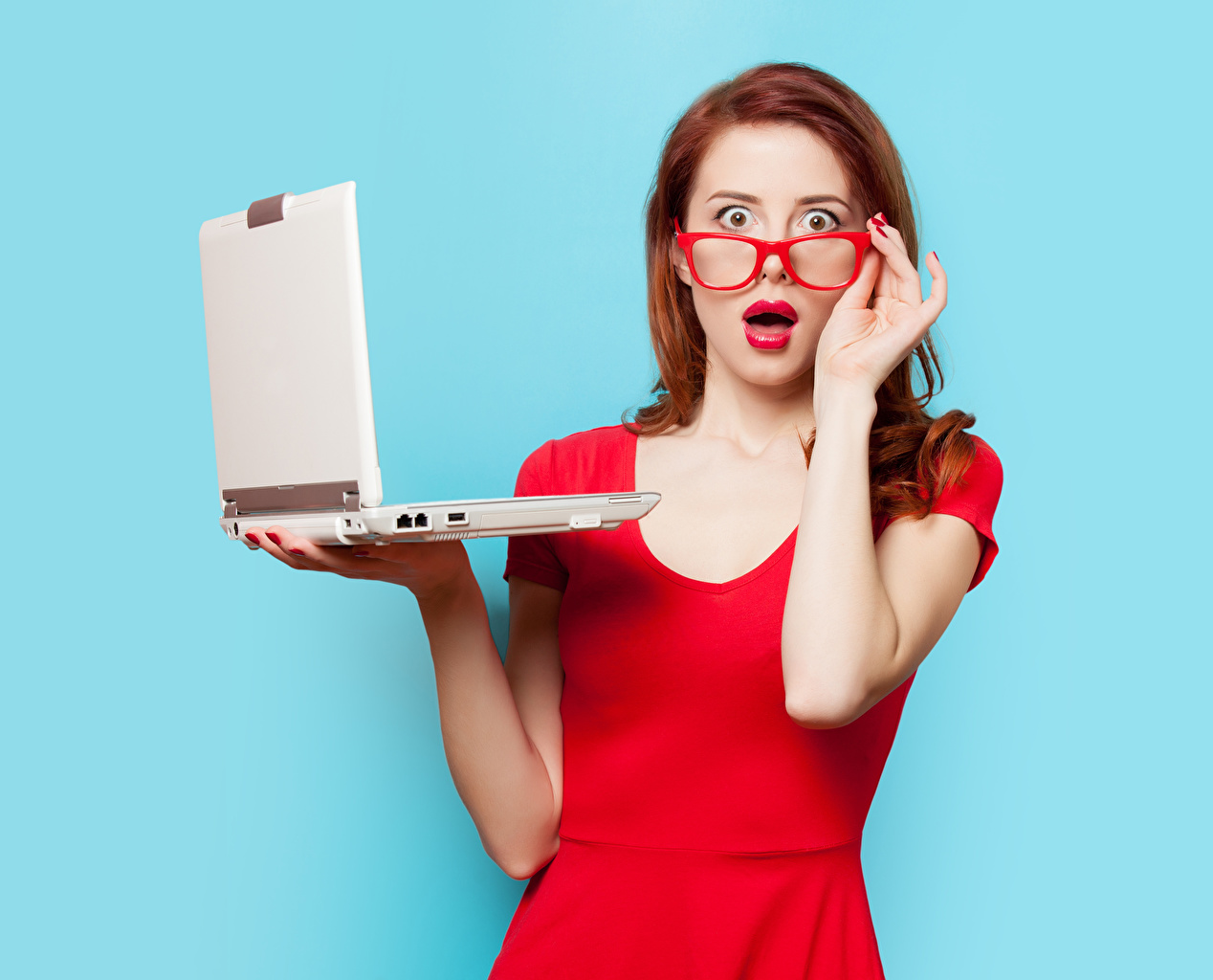 Picture Laptops Redhead girl amazement Girls Hands eyeglasses Glance Red lips Colored background surprised Surprise emotion female young woman Glasses Staring