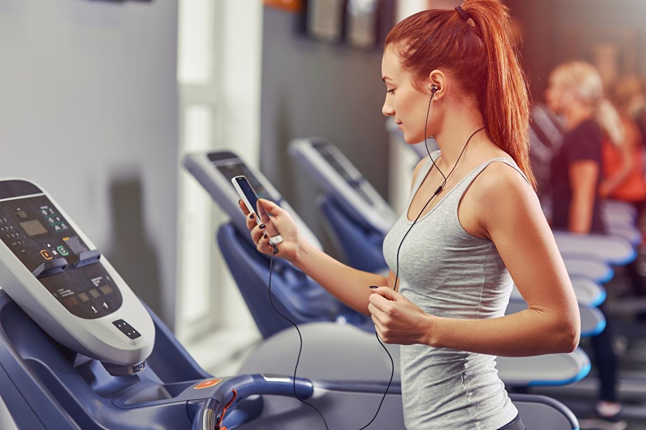 Fotos Rotschopf Kopfhörer Turnhalle Körperliche Aktivität Lauf smartphones Fitness Sport junge frau Trainieren Fitnessstudio Laufen Laufsport Smartphone Mädchens sportliches junge Frauen