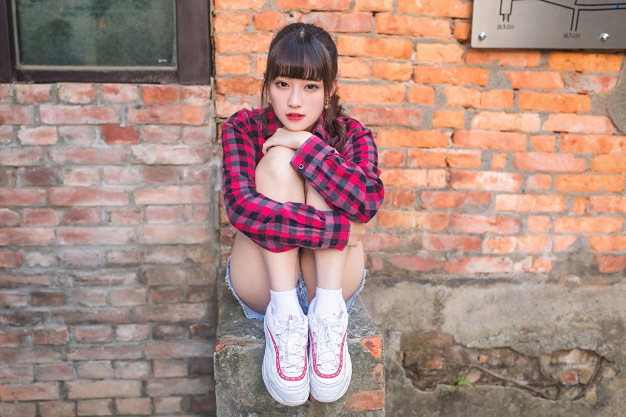 Fotos Hemd Mädchens sportschuhe Bein Aus Ziegel asiatisches wand sitzt Turnschuh junge frau junge Frauen Asiaten Asiatische aus backsteinen Mauer wände sitzen Sitzend