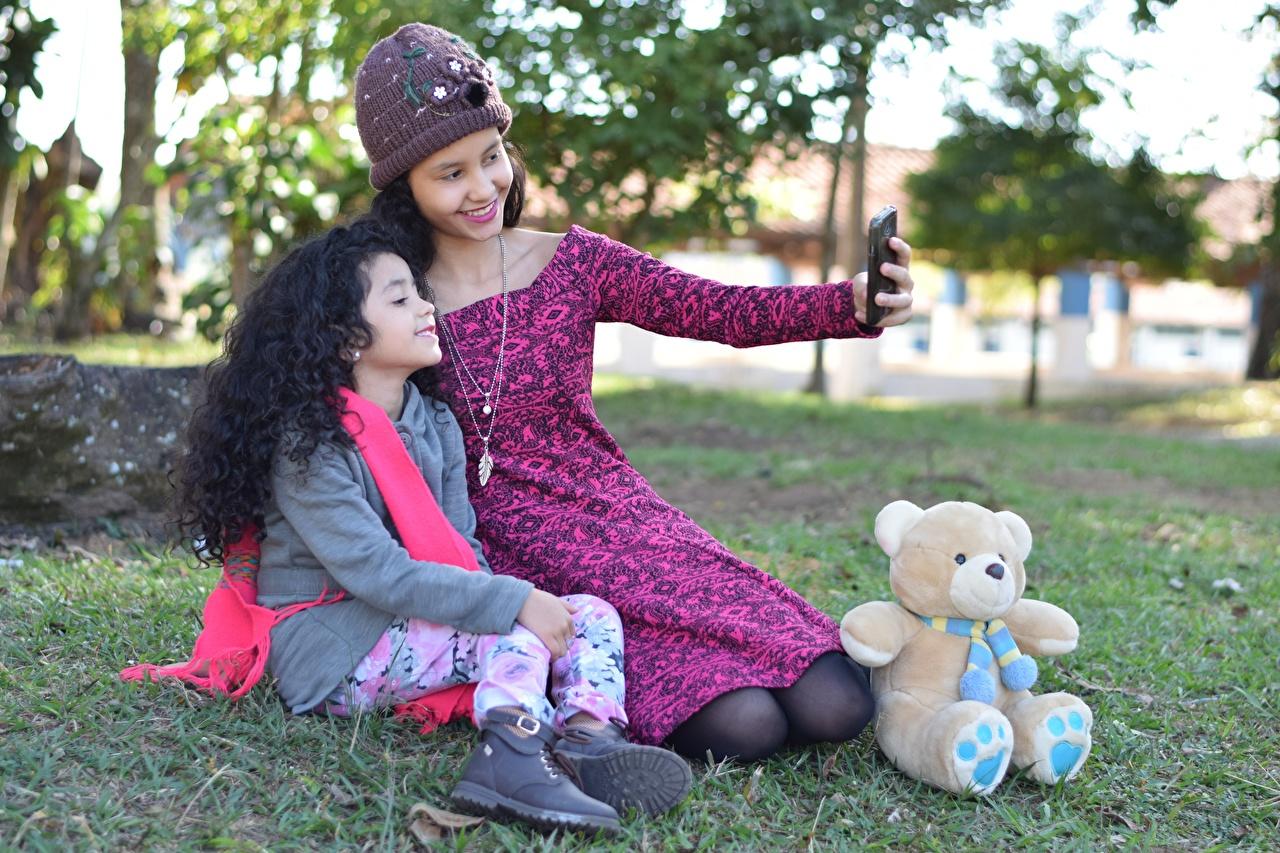Desktop Hintergrundbilder Kleine Mädchen Brünette Selfie Lächeln Mutter Kinder 2 Mütze Teddybär Gras Sitzend kind Zwei Teddy Knuddelbär sitzt sitzen