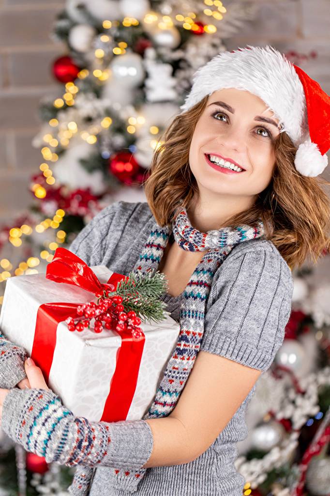 Photo Christmas Brown haired Smile Girls Winter hat Gifts Staring  for Mobile phone New year female young woman present Glance