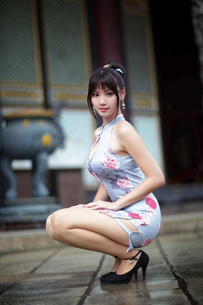 Photos Brunette girl blurred background Beautiful Girls Asiatic sit Glance Dress  for Mobile phone Bokeh female young woman Asian Sitting Staring gown frock