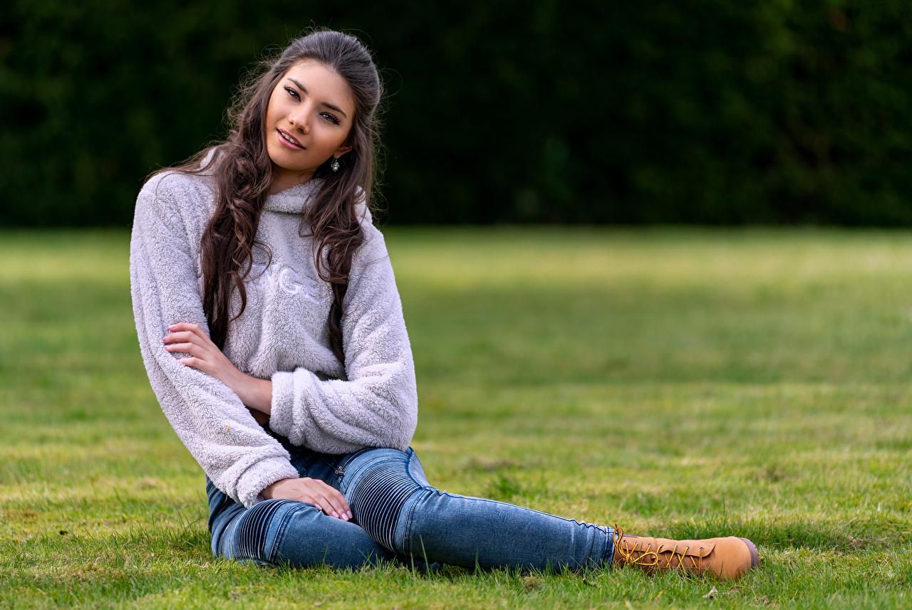 Foto Model Bokeh Mädchens Jeans Sweatshirt Gras Sitzend Starren unscharfer Hintergrund junge frau junge Frauen sitzt sitzen Blick