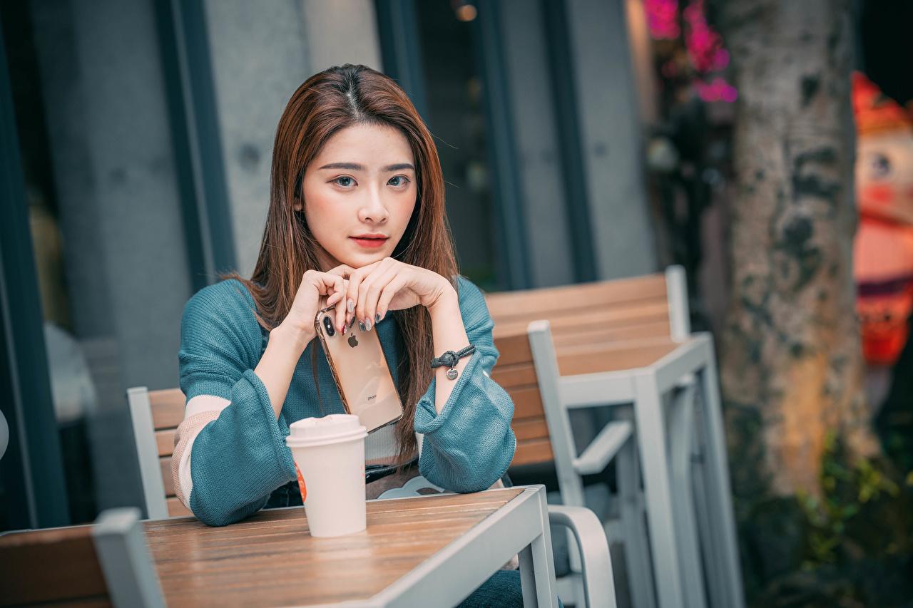 Desktop Hintergrundbilder Apple Braunhaarige smartphones Bokeh junge frau Asiatische Hand Tisch Starren Braune Haare Smartphone unscharfer Hintergrund Mädchens junge Frauen Asiaten asiatisches Blick