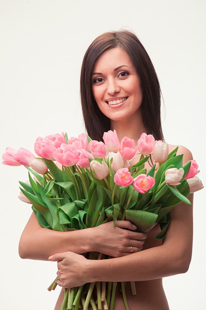 zdjęcie Szatenka Uśmiech Tulipany Dziewczyny Ręce wzrok Szare tło  dla Telefon komórkowy brązowowłosa dziewczyna dziewczyna z brązowymi włosami tulipan dziewczyna młoda kobieta młode kobiety Spojrzenie na szarym tle
