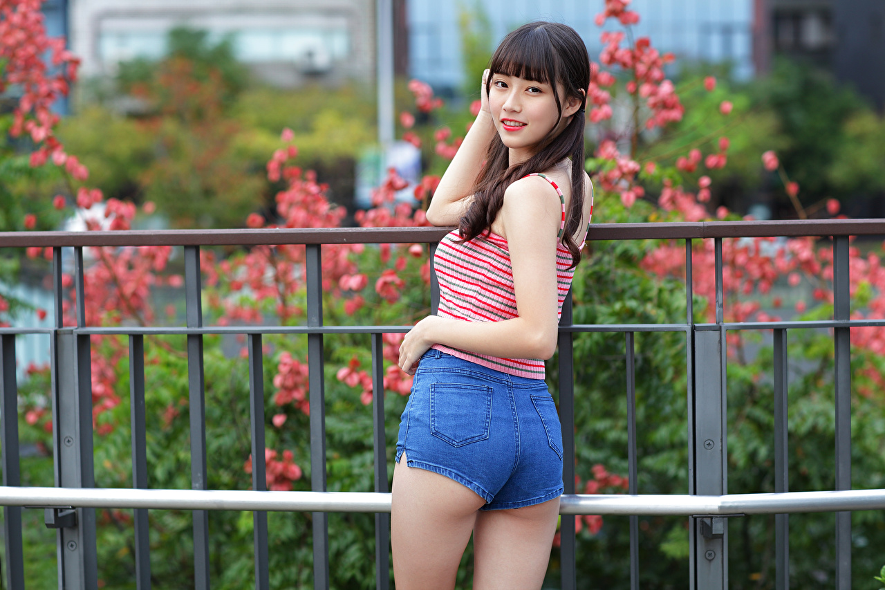 Desktop Wallpapers Pose young woman Asian Fence Sleeveless shirt Shorts Staring posing Girls female Asiatic Singlet Glance