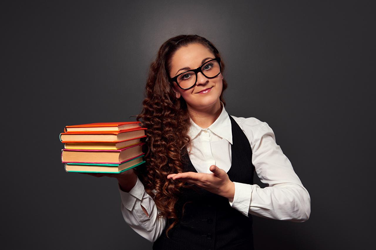 Fotos von Braunhaarige Lächeln Lockige Mädchens Buch Hand Brille Blick Grauer Hintergrund Braune Haare locken junge frau junge Frauen Bücher Starren