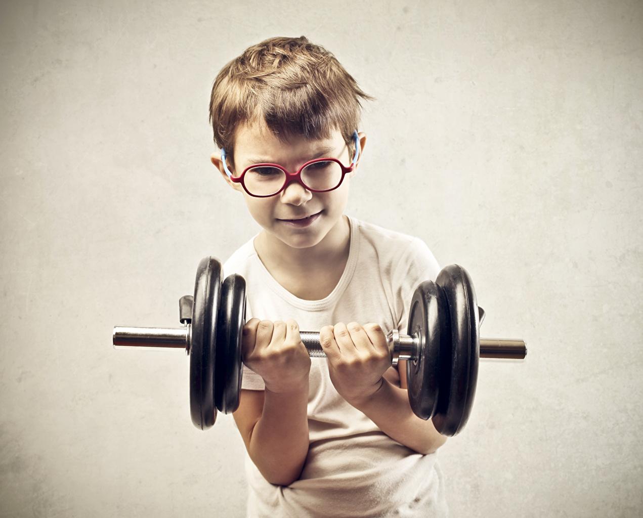 Foto jungen Körperliche Aktivität kind Hanteln Hand Brille Grauer Hintergrund Junge Trainieren Kinder Hantel