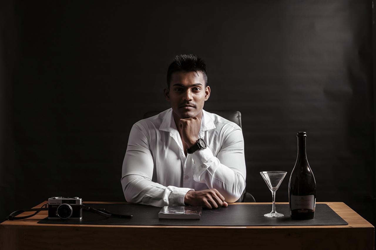 Fotos von Indian Mann Fotoapparat Hemd Hand sitzen Flasche Weinglas Starren sitzt Sitzend flaschen Blick
