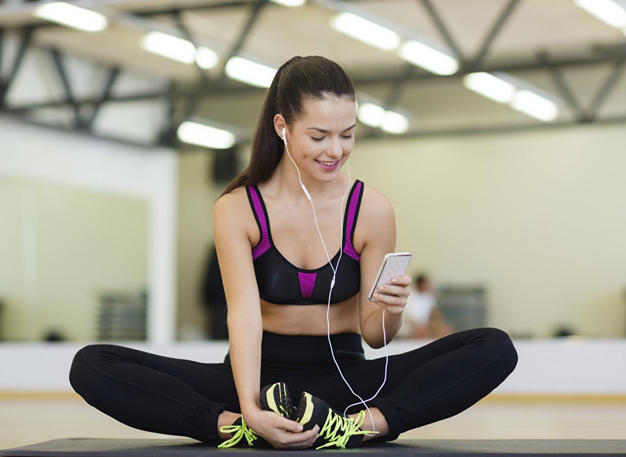 Foto Brünette Kopfhörer Lächeln Smartphone unscharfer Hintergrund posiert Fitness junge frau Bein Hand sitzt smartphones Bokeh Pose Mädchens junge Frauen sitzen Sitzend