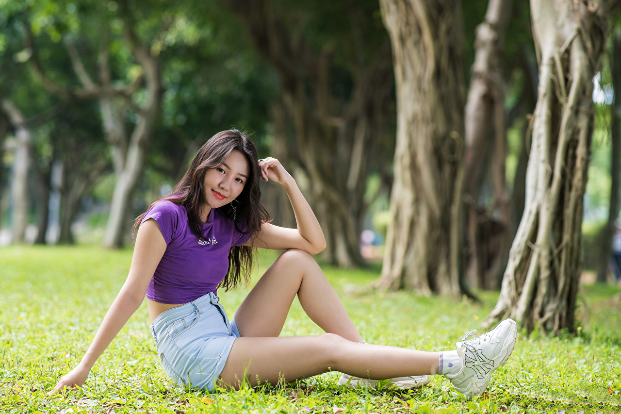 Photos Smile female T-shirt Legs Asian Grass Shorts Sitting Glance Girls young woman Asiatic sit Staring