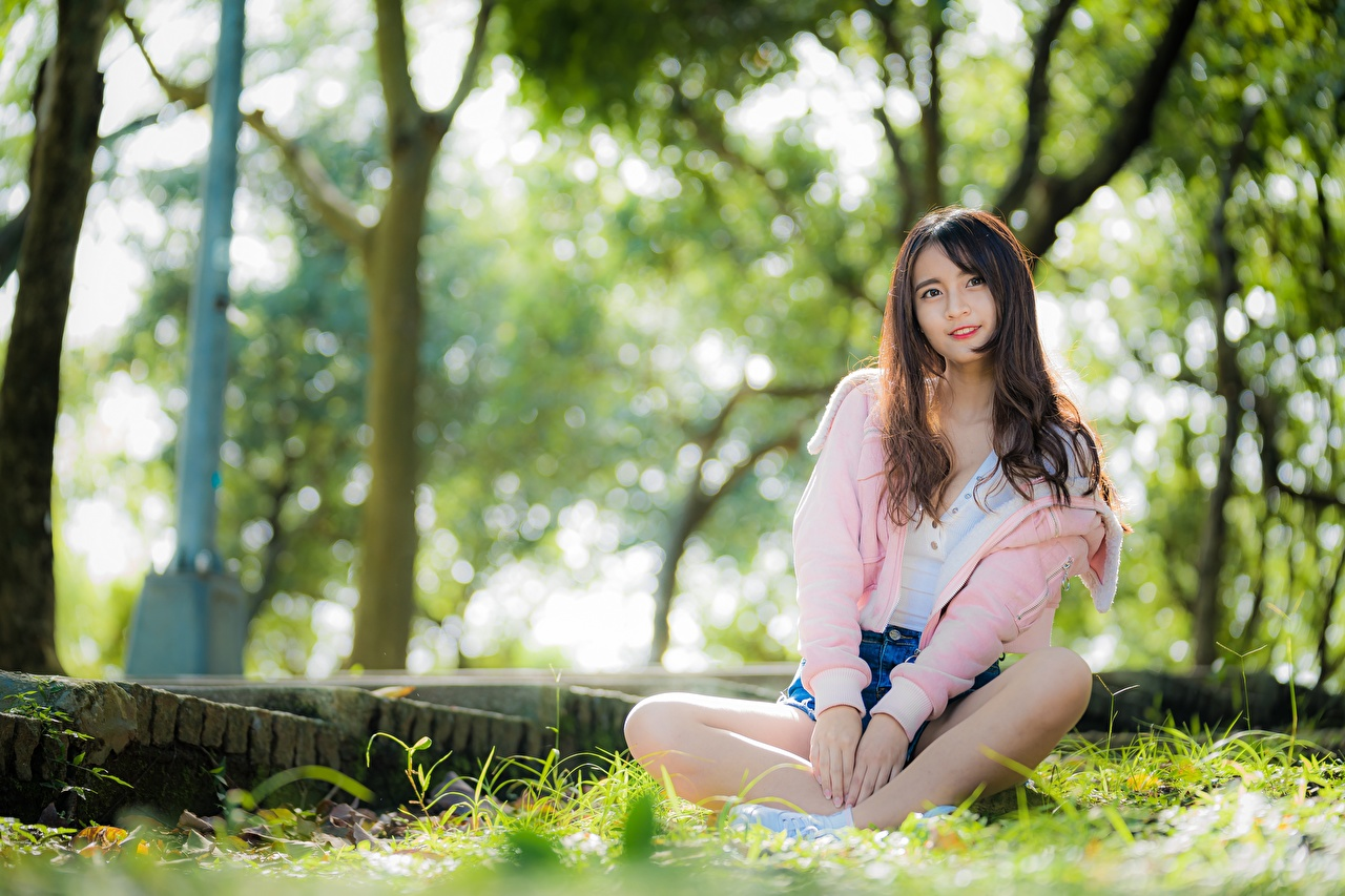 Image Brown haired Smile blurred background young woman Asiatic sit Hands Grass Bokeh Girls female Asian Sitting
