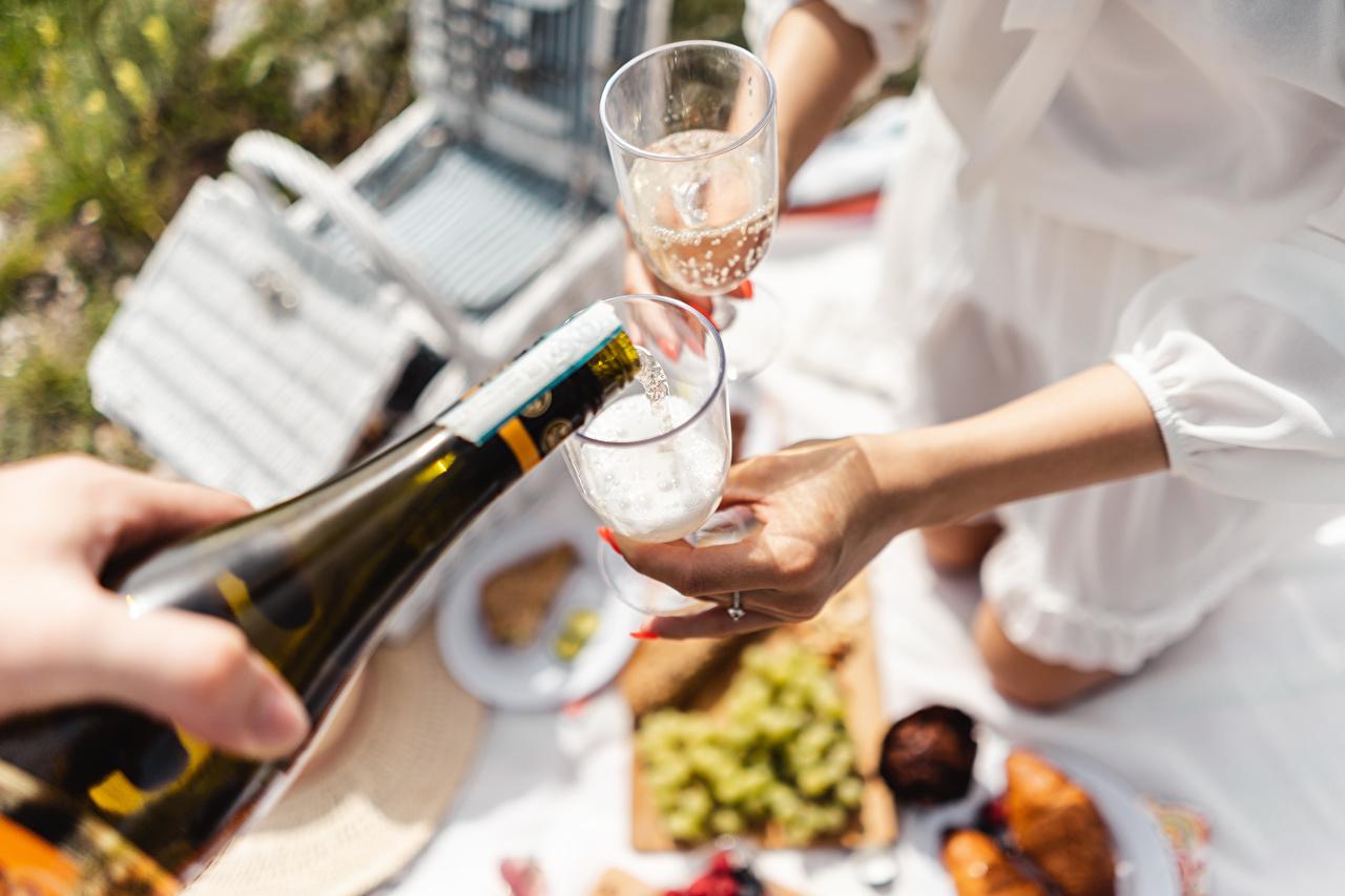 Fotos von Picknick Bokeh Champagner Hand Flasche Weinglas Lebensmittel unscharfer Hintergrund Schaumwein flaschen das Essen