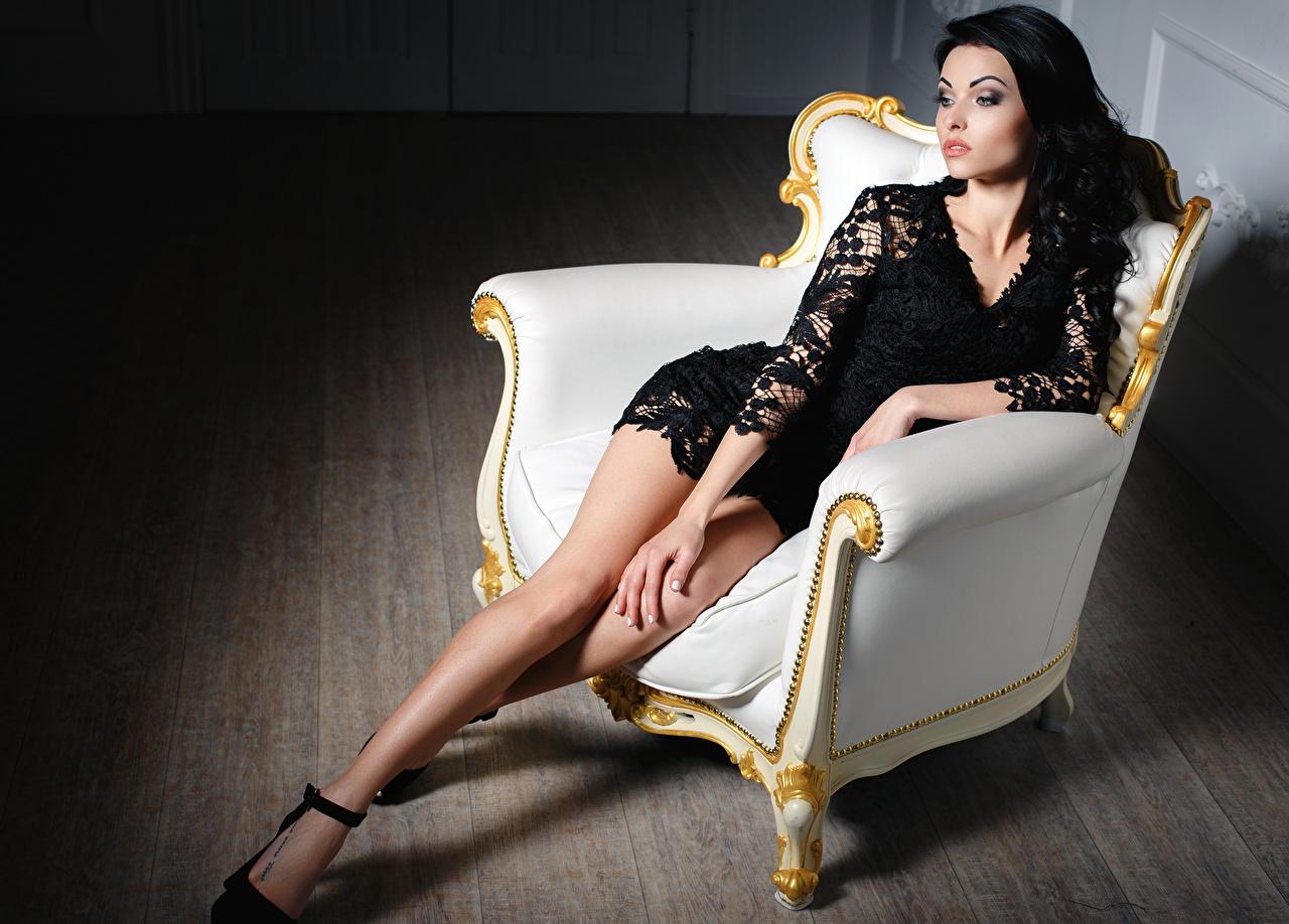 Desktop Wallpapers Brunette girl Girls Legs sit Wing chair frock female young woman Sitting Armchair gown Dress