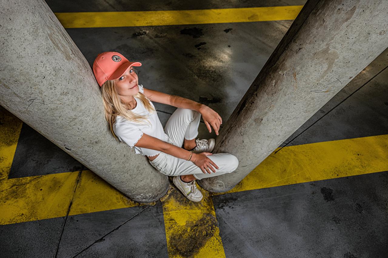 Skrivebordsbakgrunn Blond jente Smil Posere Unge kvinner Sitter Blikk Baseball cap Blonde ung kvinne ser