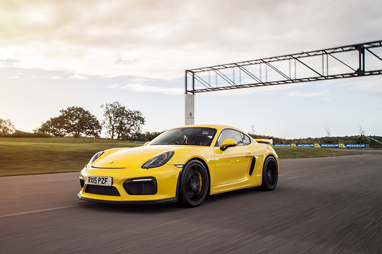 Photo Porsche Cayman GT4 Yellow Motion auto moving riding driving at speed Cars automobile