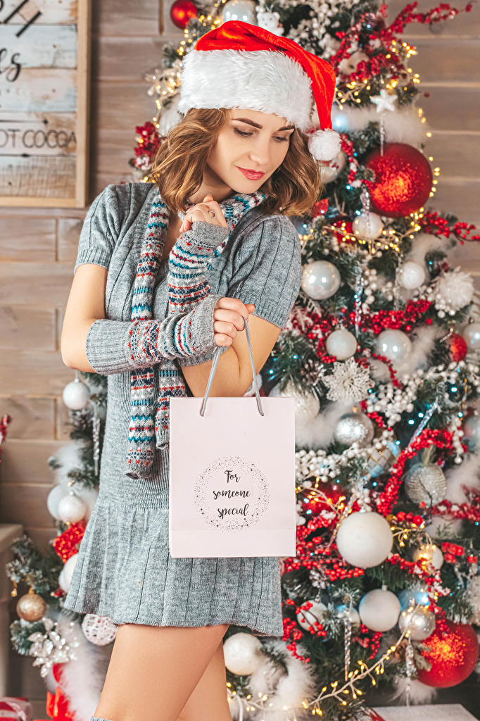 Images New year Brown haired female Winter hat Christmas tree present Balls Dress  for Mobile phone Christmas Girls young woman New Year tree Gifts gown frock
