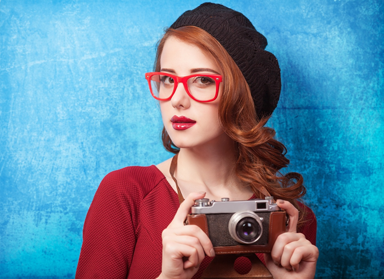 Desktop Wallpapers Redhead girl Camera Photographer Beret female Hands Glasses Staring Colored background Girls young woman eyeglasses Glance