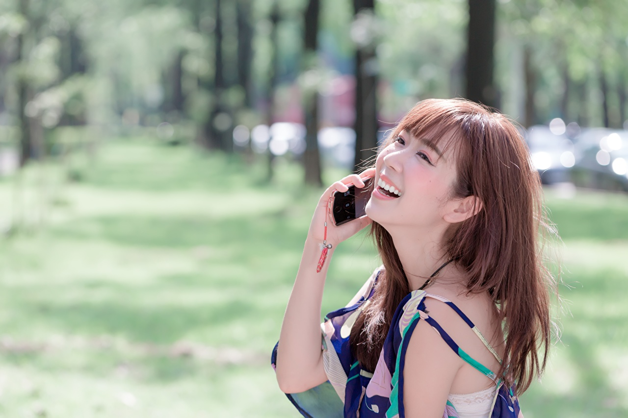 Images Brown haired laughs Bokeh Girls Telephone Asiatic Hands laugh Laughter blurred background phone female young woman Asian