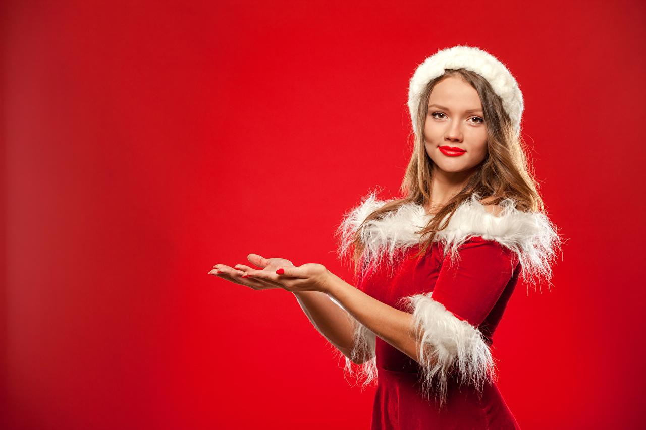 Bilder Neujahr Braune Haare Mädchens Hand Uniform Blick Roter Hintergrund Braunhaarige Starren