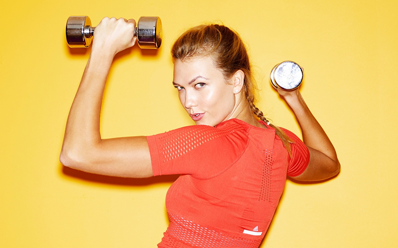 Desktop Wallpapers Karlie Kloss Brown haired Fitness Dumbbells young woman Hands Glance Celebrities Colored background Girls female dumbbell Staring