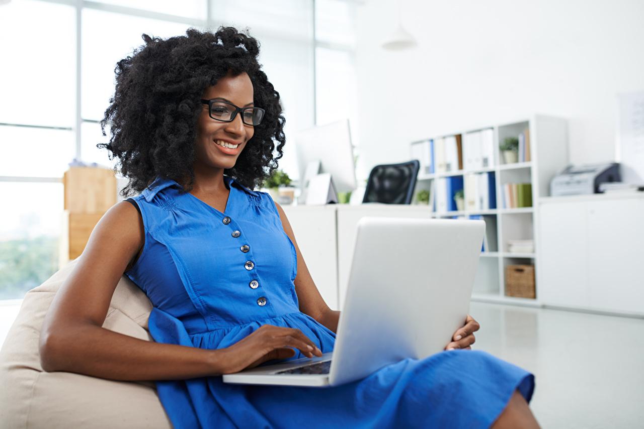Hintergrundbilder Notebook Brünette Lächeln Neger Mädchens Brille Sitzend sitzt sitzen