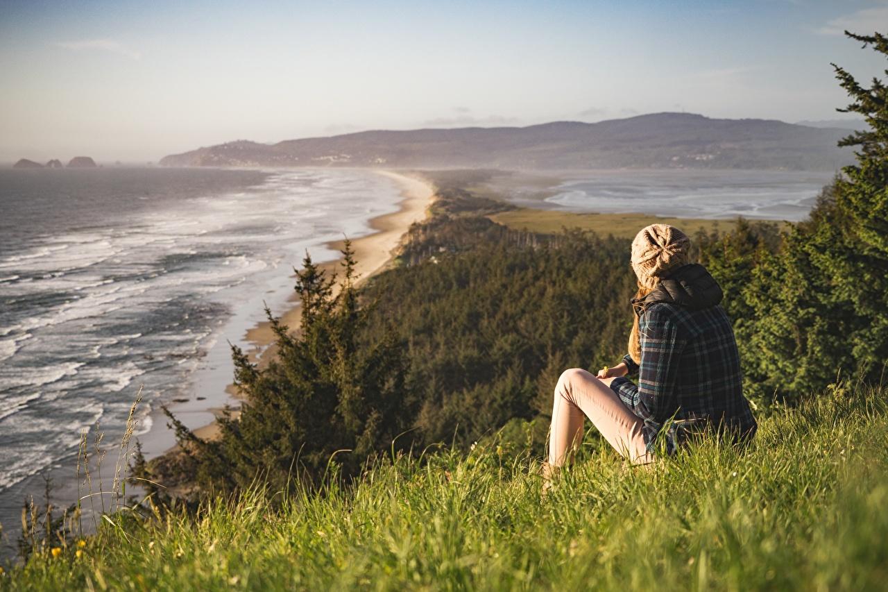 Desktop Hintergrundbilder Meer Natur Mütze Mädchens Gras sitzt Küste junge frau junge Frauen sitzen Sitzend