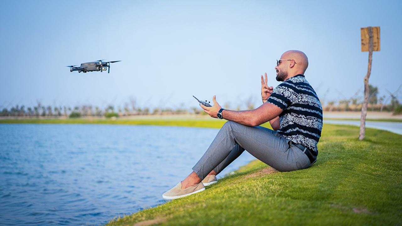 Bilder Quadrokopter Mann kahle Gras Sitzend Quadrocopter Glatze kahlköpfiger sitzt sitzen