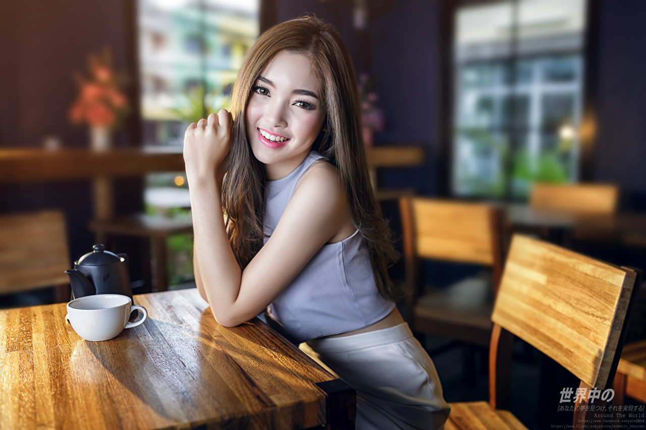 Images Brown haired Smile Bokeh Cafe Girls Asiatic Cup Hands Sitting Glance blurred background female young woman Asian sit Staring
