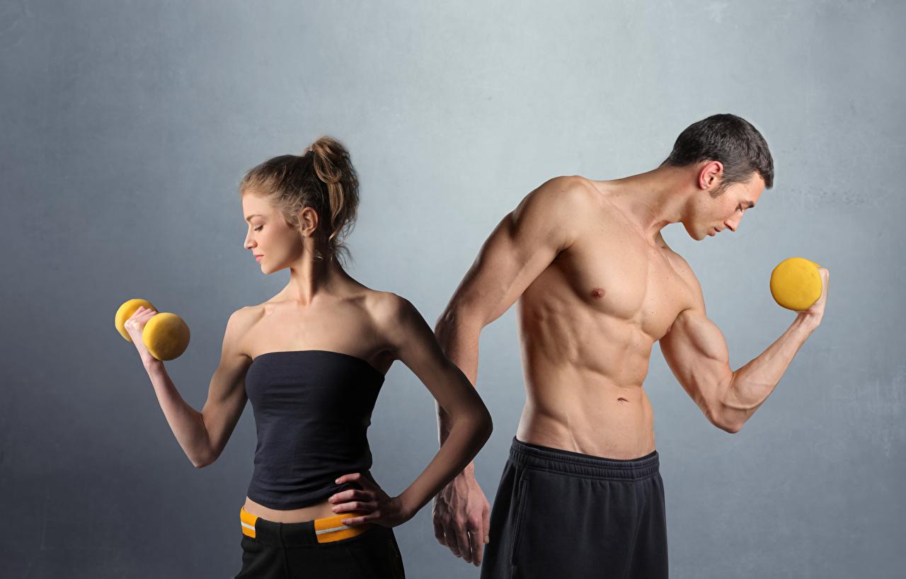 Fotos von Mann Muskeln Fitness 2 Hanteln sportliches Grauer Hintergrund Zwei Sport Hantel