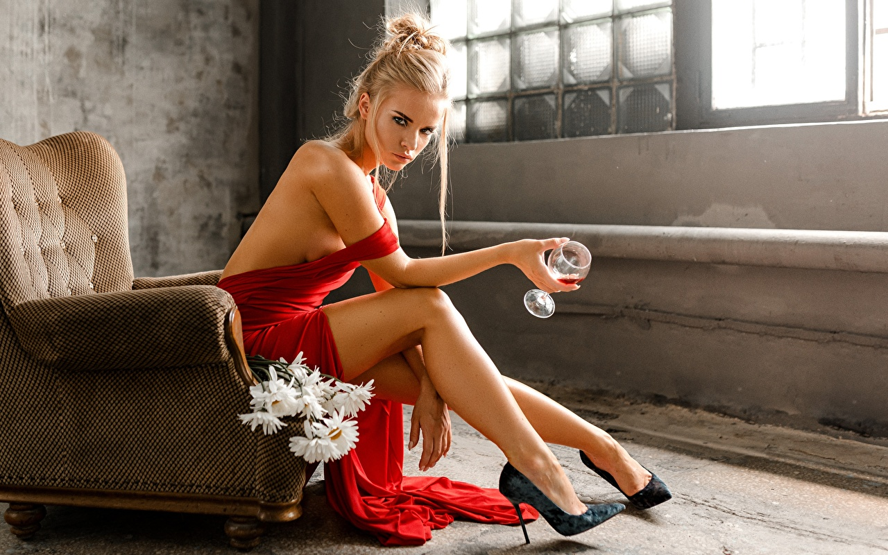 Photo Blonde girl Svetlana, Evgeny Markalev Pose Girls Legs sit Hands Stemware Wing chair Stilettos posing female young woman Sitting Armchair high heels