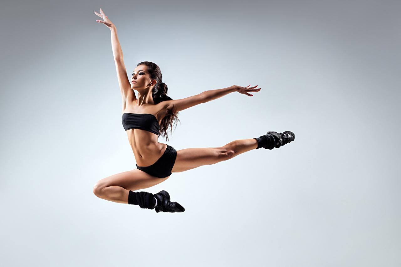 Foto Tanzen Pose junge frau Bein Sprung Hand Grauer Hintergrund Tanz posiert Mädchens junge Frauen