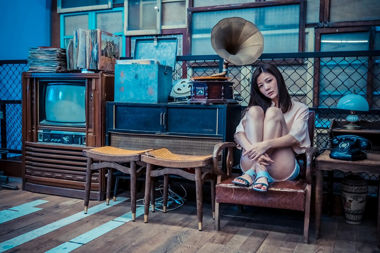 Asiático Poltrona Sentados Pernas Ver Telefone Televisor Lâmpada Registro de gramofone jovem mulher, mulheres jovens, moça, asiática, sentada, televisão Meninas