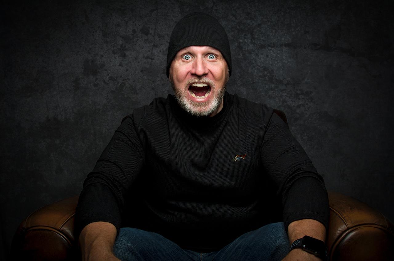 Bilder Mann Staunen Furcht bärtige Mütze T-Shirt Sitzend Starren Erstaunen überrascht überraschte Überraschung überraschter überraschtes Angst erschrecken bärte Barthaar bärtiger sitzt sitzen Blick