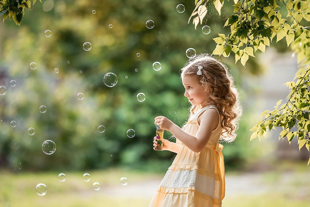 Fotos von Kleine Mädchen Seifenblasen unscharfer Hintergrund kind Bokeh Kinder