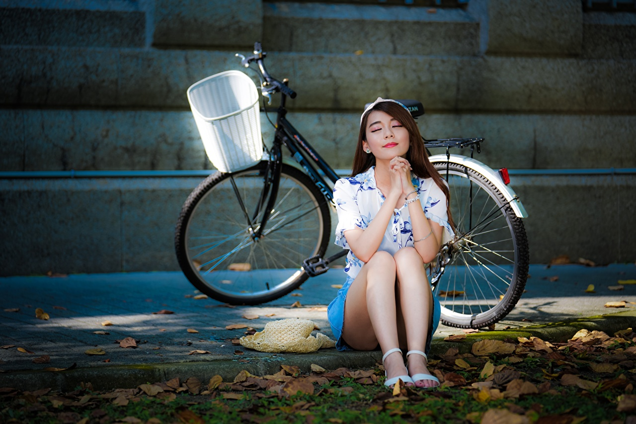 Photos Brown haired Bicycle Hat young woman Legs Asiatic sit Hands bike bicycles Girls female Asian Sitting