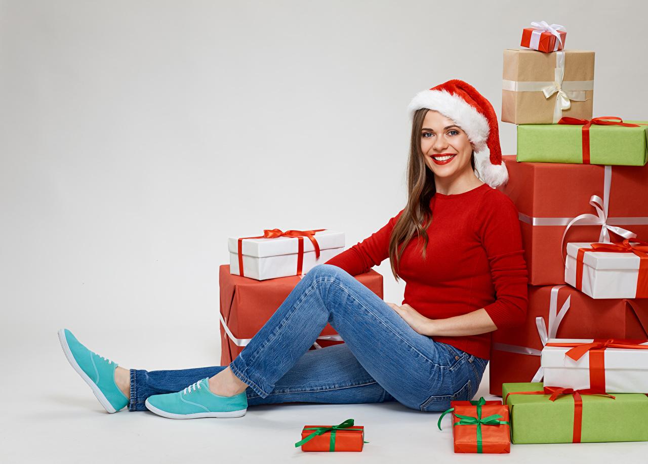 Foto Neujahr Braunhaarige Lächeln Mütze junge Frauen Jeans Geschenke sitzen Starren Grauer Hintergrund Braune Haare Mädchens junge frau sitzt Sitzend Blick