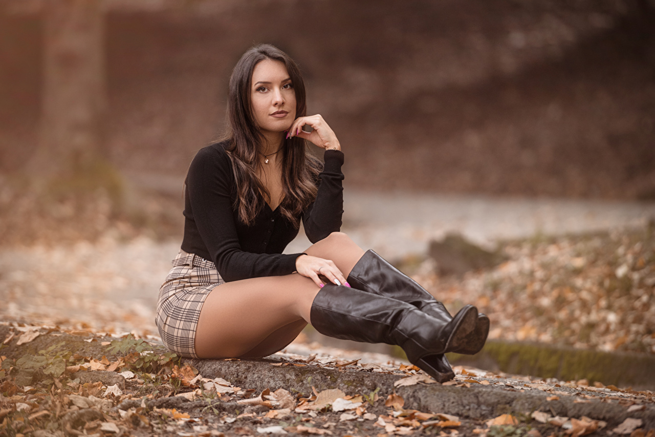 Images Skirt Foliage Brown haired Wearing boots blurred background Blouse female sit Staring Leaf Bokeh Girls young woman Sitting Glance