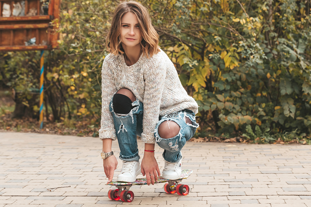 Photo Brown haired female Sweater Skateboard Hands Staring Girls young woman Glance