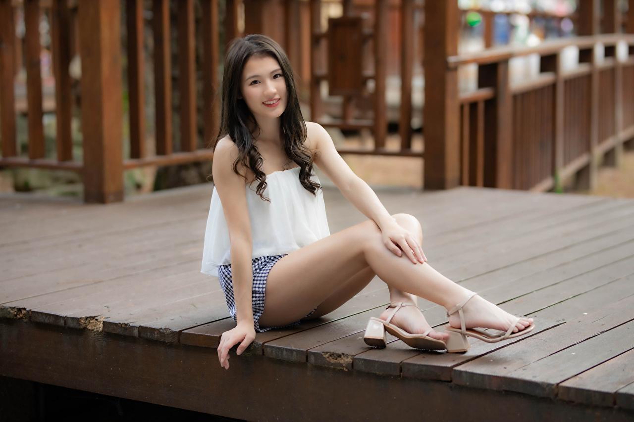 Fotos Lächeln junge frau Bein asiatisches Sitzend Blick Mädchens junge Frauen Asiaten Asiatische sitzt sitzen Starren