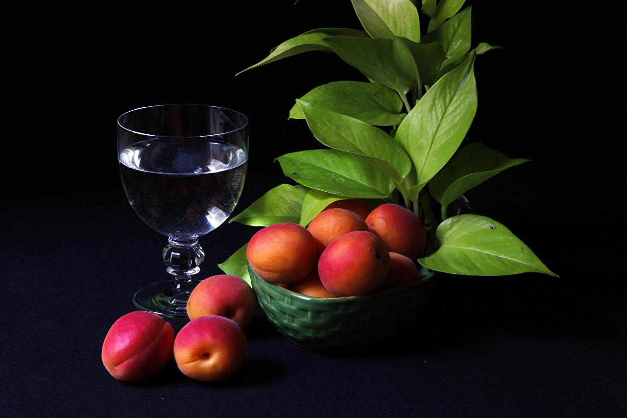 Photos Foliage Apricot Bowl Food Stemware Black background Drinks Leaf drink