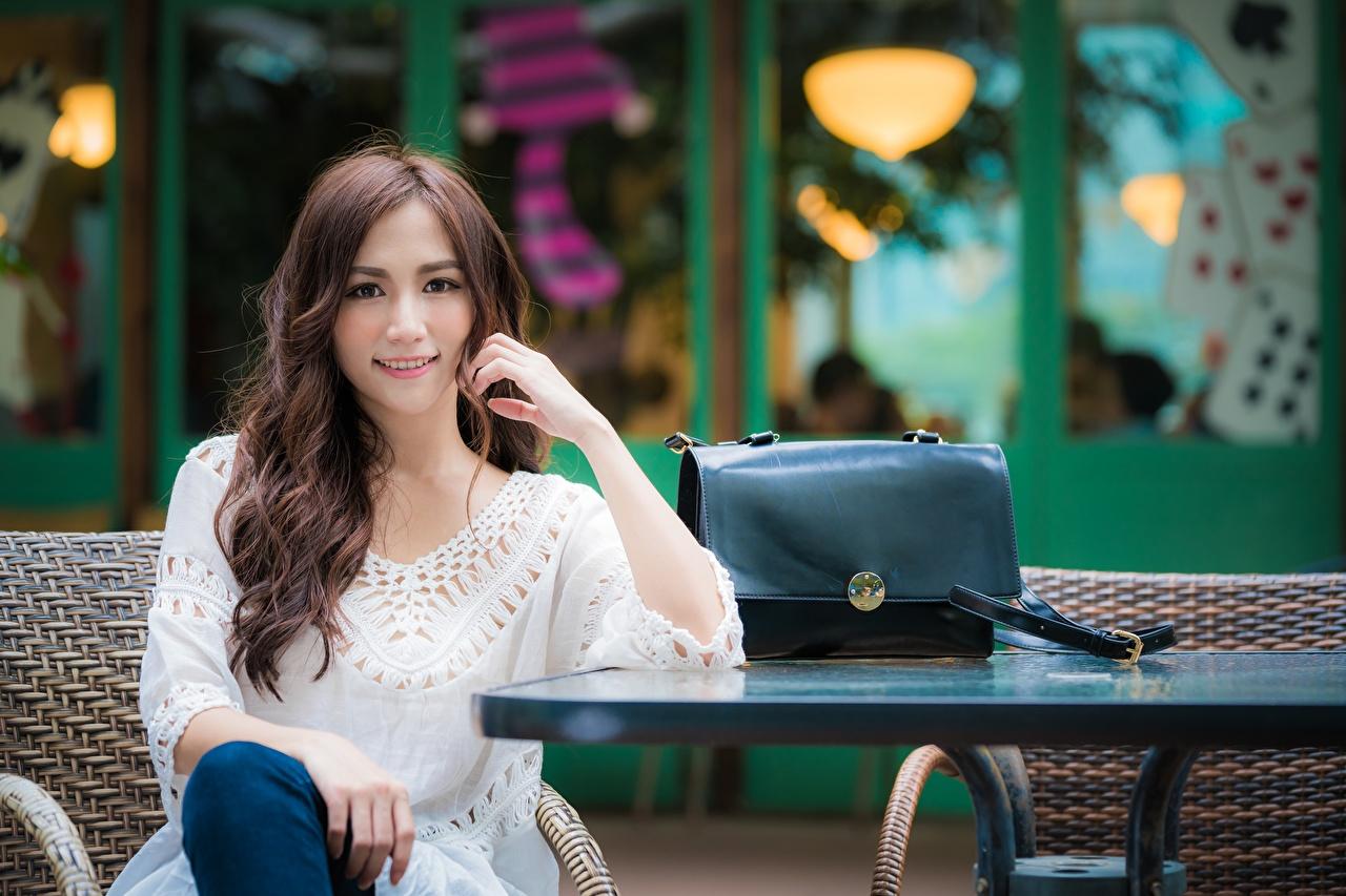 Desktop Hintergrundbilder Braunhaarige Lächeln unscharfer Hintergrund Mädchens Asiatische Hand Sitzend Handtasche Blick Braune Haare Bokeh junge frau junge Frauen Asiaten asiatisches sitzt sitzen Starren