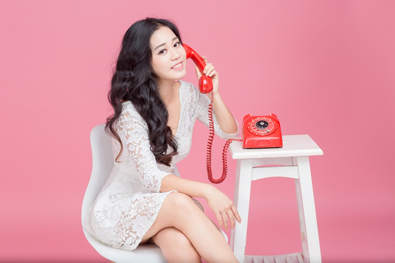 Pictures Brunette girl Smile phone Girls Asian sit Hands Pink background frock female Telephone young woman Asiatic Sitting gown Dress