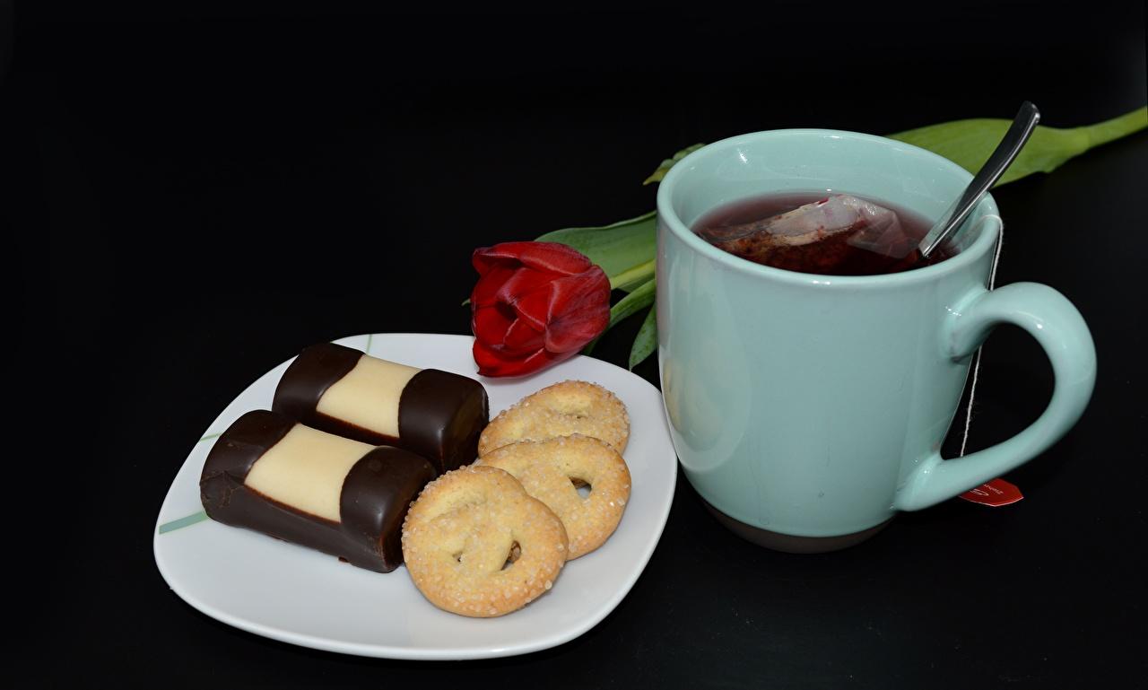 Foto Tee Tulpen Kekse Teller Becher Lebensmittel Schwarzer Hintergrund das Essen