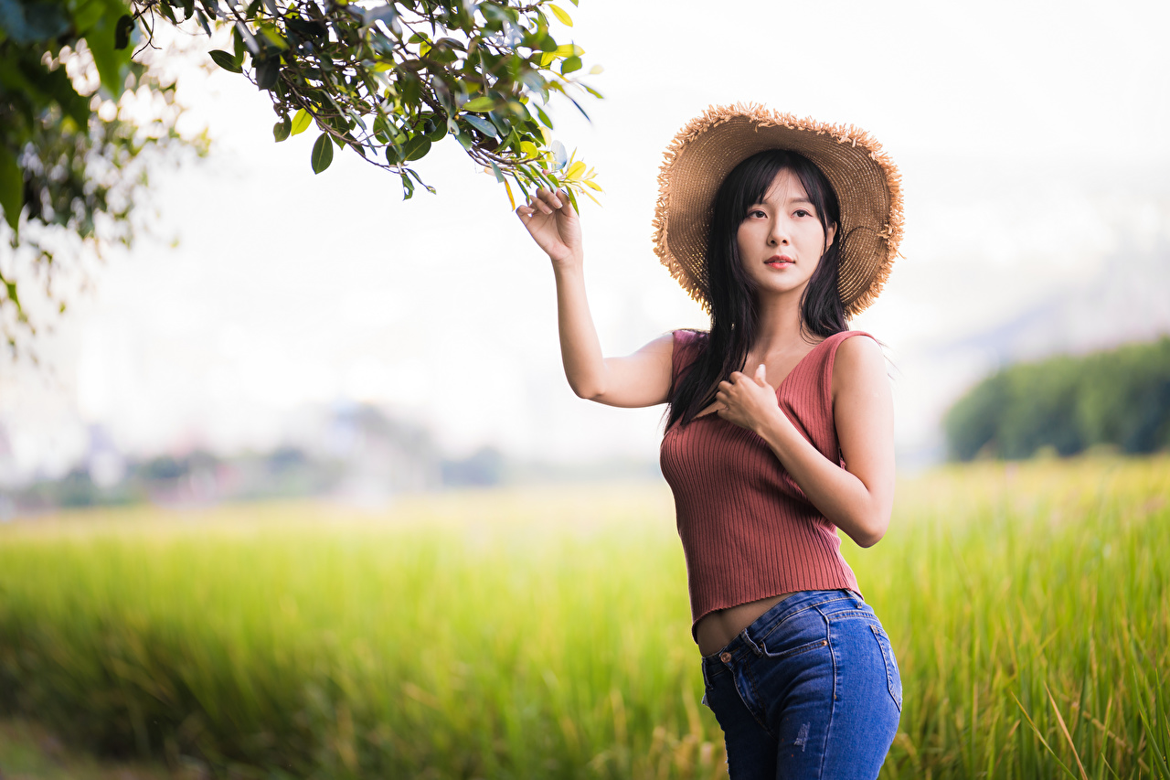 Image blurred background posing Hat young woman Jeans Asiatic Singlet Staring Bokeh Pose Girls female Asian Sleeveless shirt Glance
