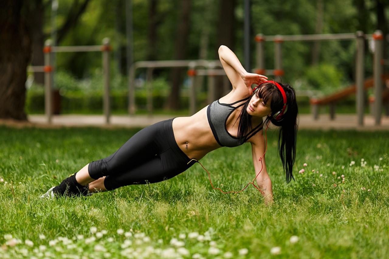 Fotos Brünette Kopfhörer Trainieren Fitness Mädchens Bein Gras Hand Bauch Körperliche Aktivität junge frau junge Frauen