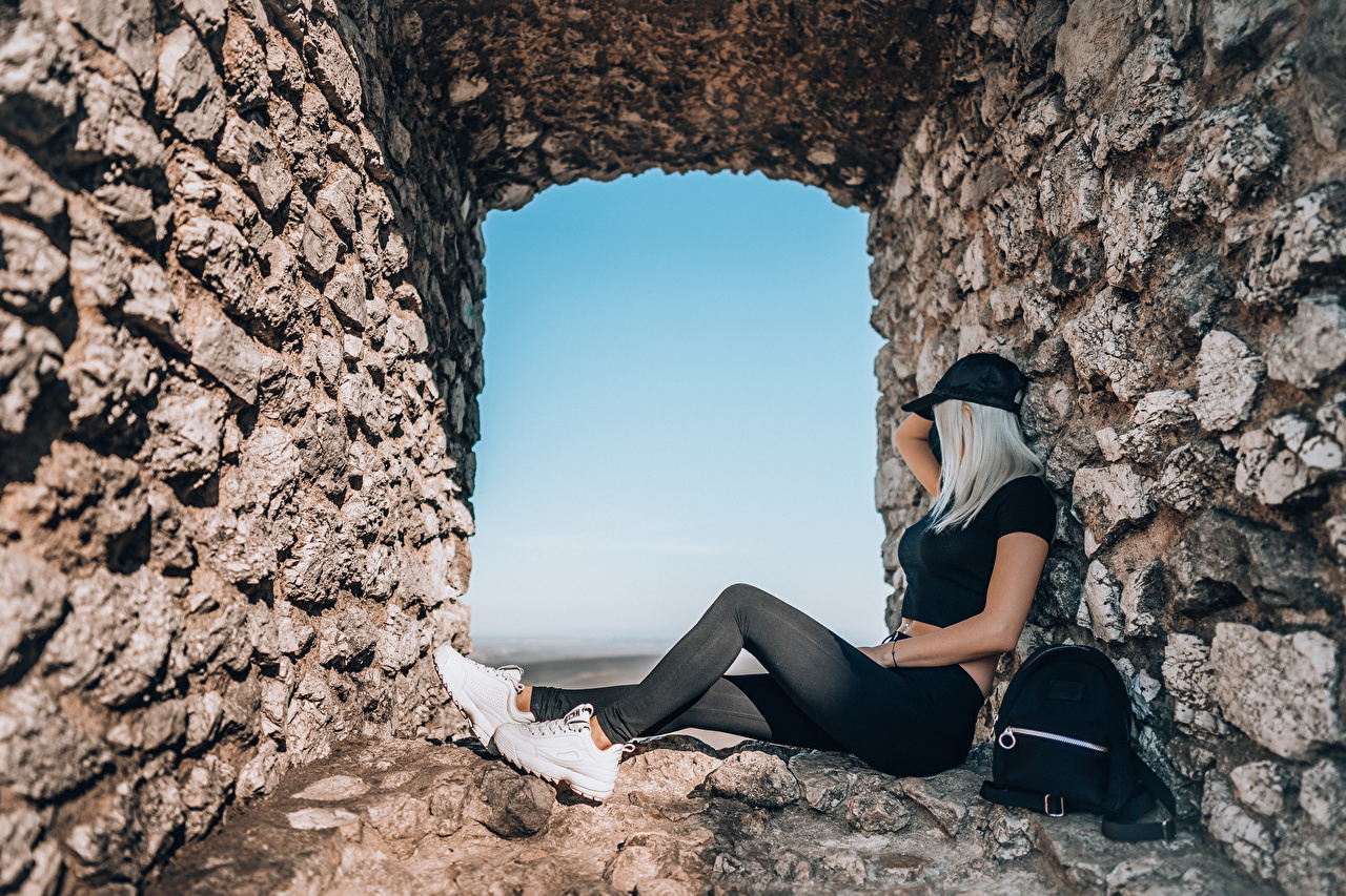 Pictures Blonde girl trainers young woman Legs walls Window Sitting Made of stone Baseball cap Girls female sneakers Athletic shoe sit Wall