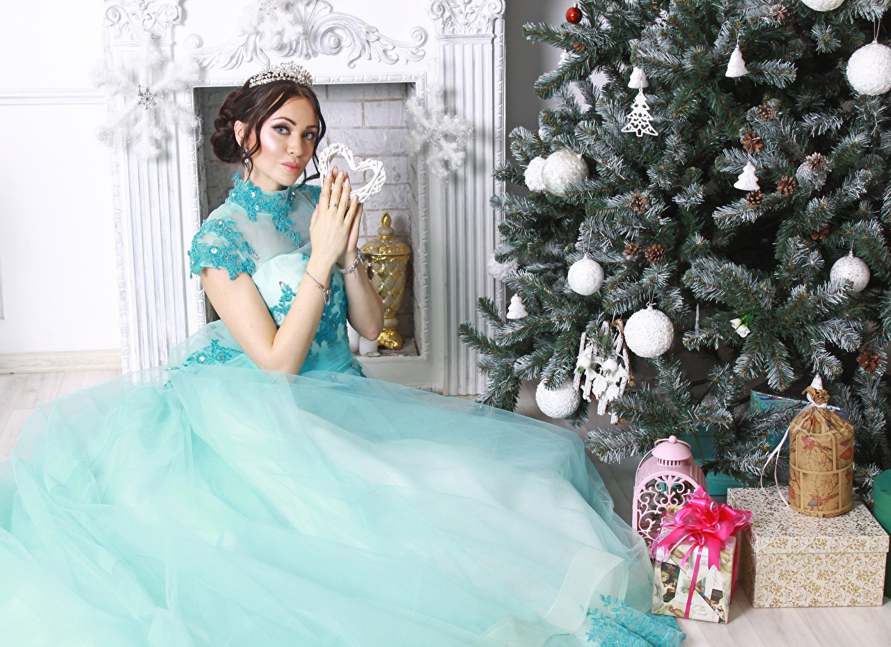 Photo New year Brown haired Girls Christmas tree Gifts sit frock Christmas female young woman New Year tree present Sitting gown Dress
