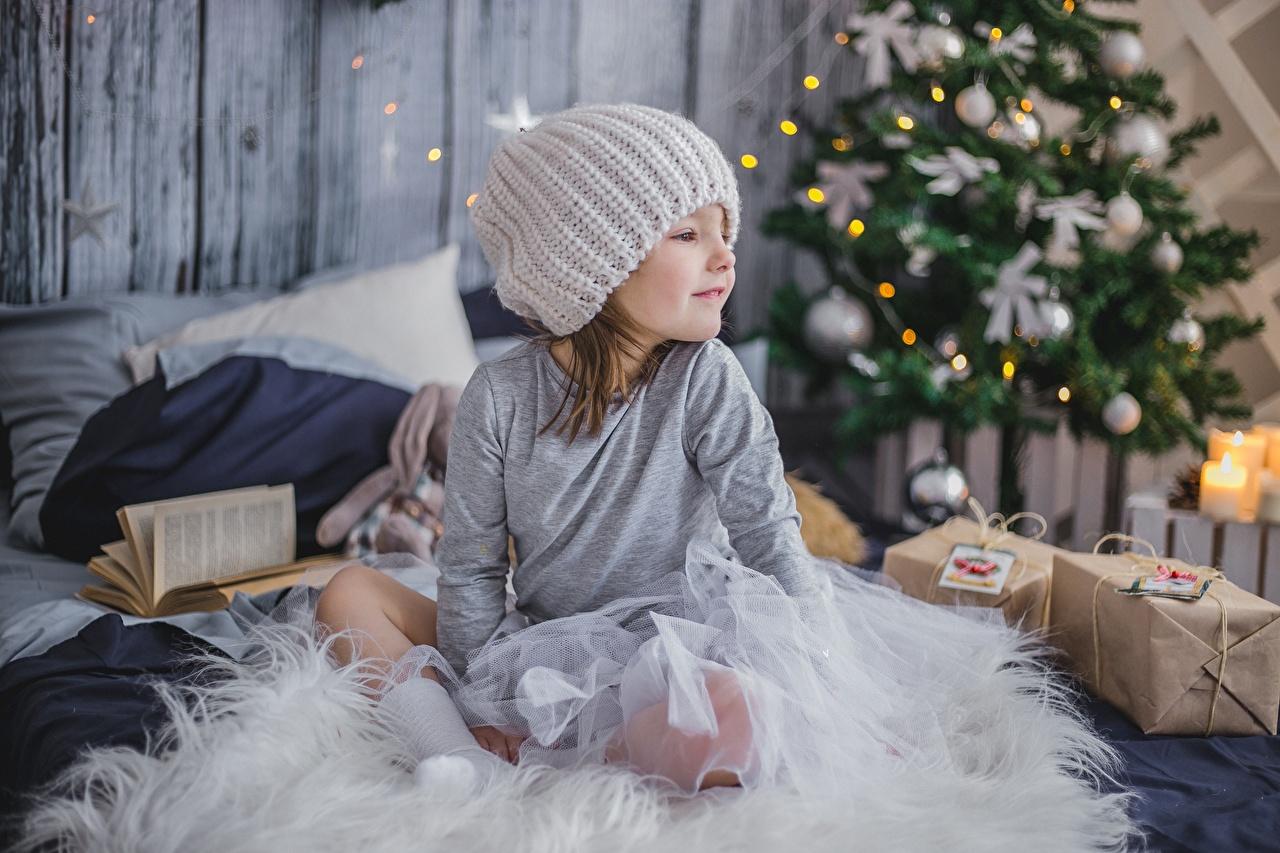 Fotos von Kleine Mädchen Neujahr Kinder Mütze Geschenke Sitzend sitzt sitzen