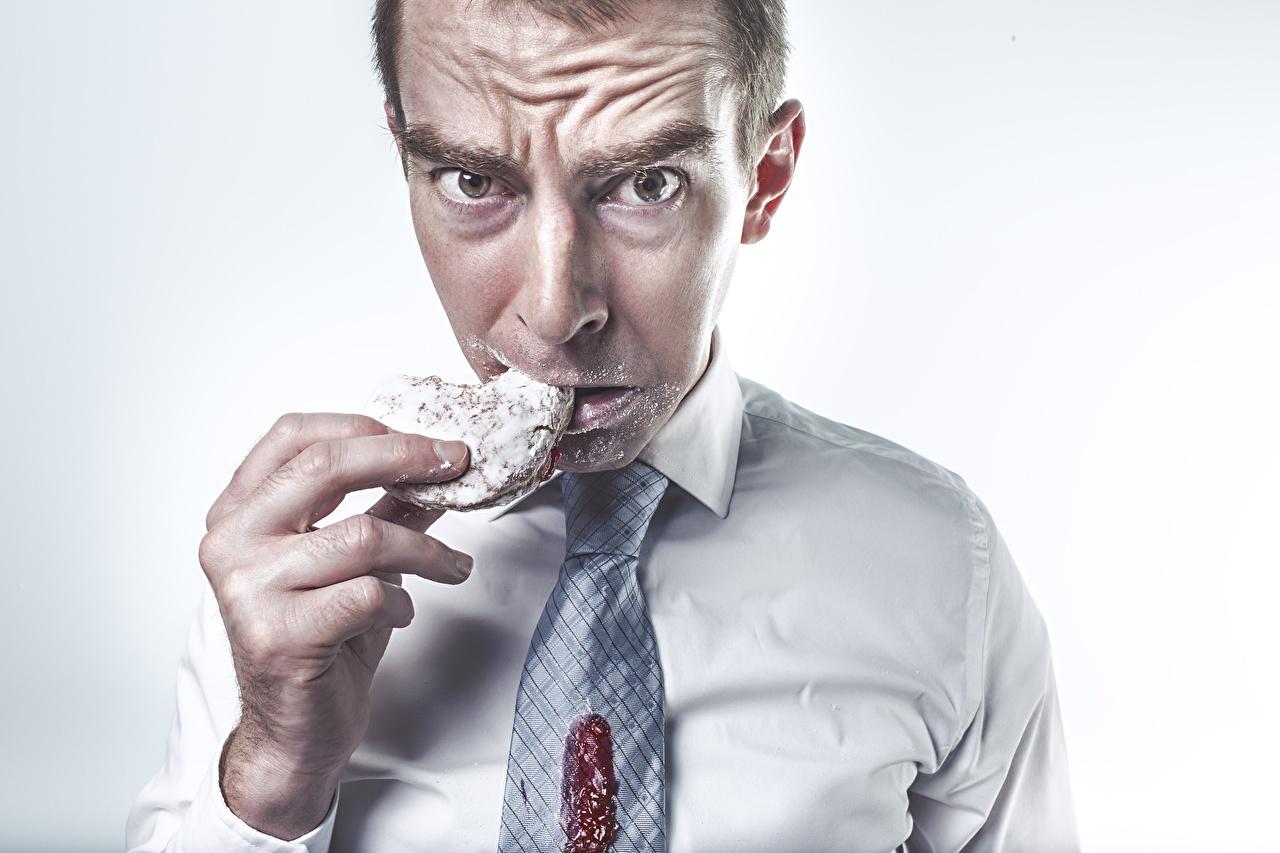 Foto Mann Krawatte Hand Kekse Finger Blick Grauer Hintergrund Starren